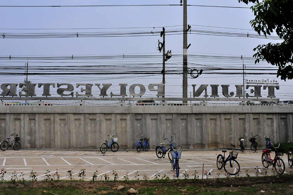 "A photograph shows a tall, concrete wall with a number of bikes in front of it. Behind it, tall letters can be seen, spelling ""Teijin Polyester"" backwards."