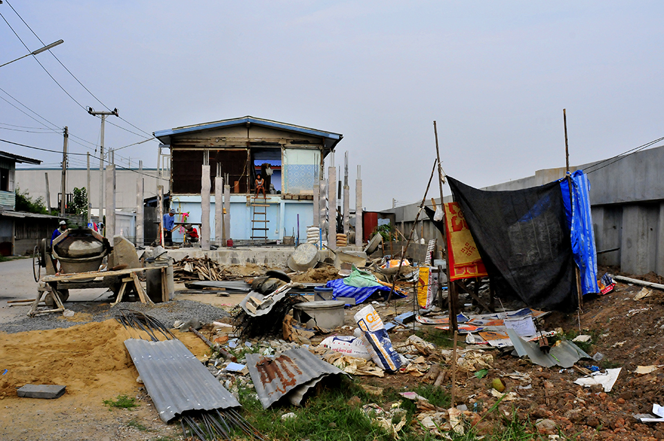 A photograph shows a great deal of debris and a house in the midst of rebuilding. To the right, concrete walls can be seen.