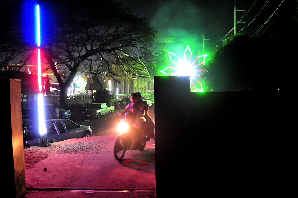 A photograph shows a wall with an opening in it. Two people on a motorcycle are driving toward the gap in the wall. Bright festive lights can be seen in the background.