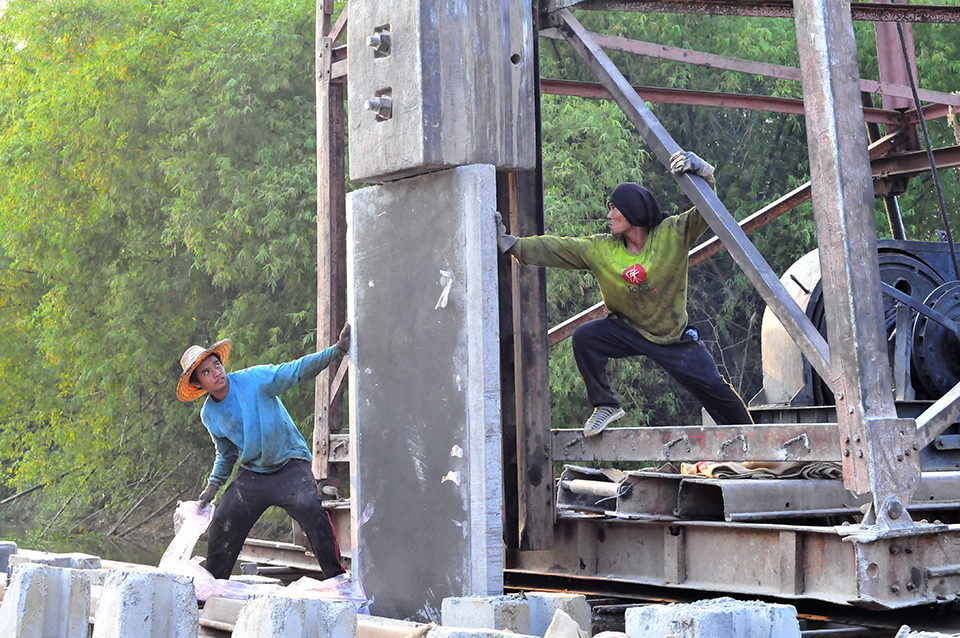 A photograph of two workers putting together a concrete structure.