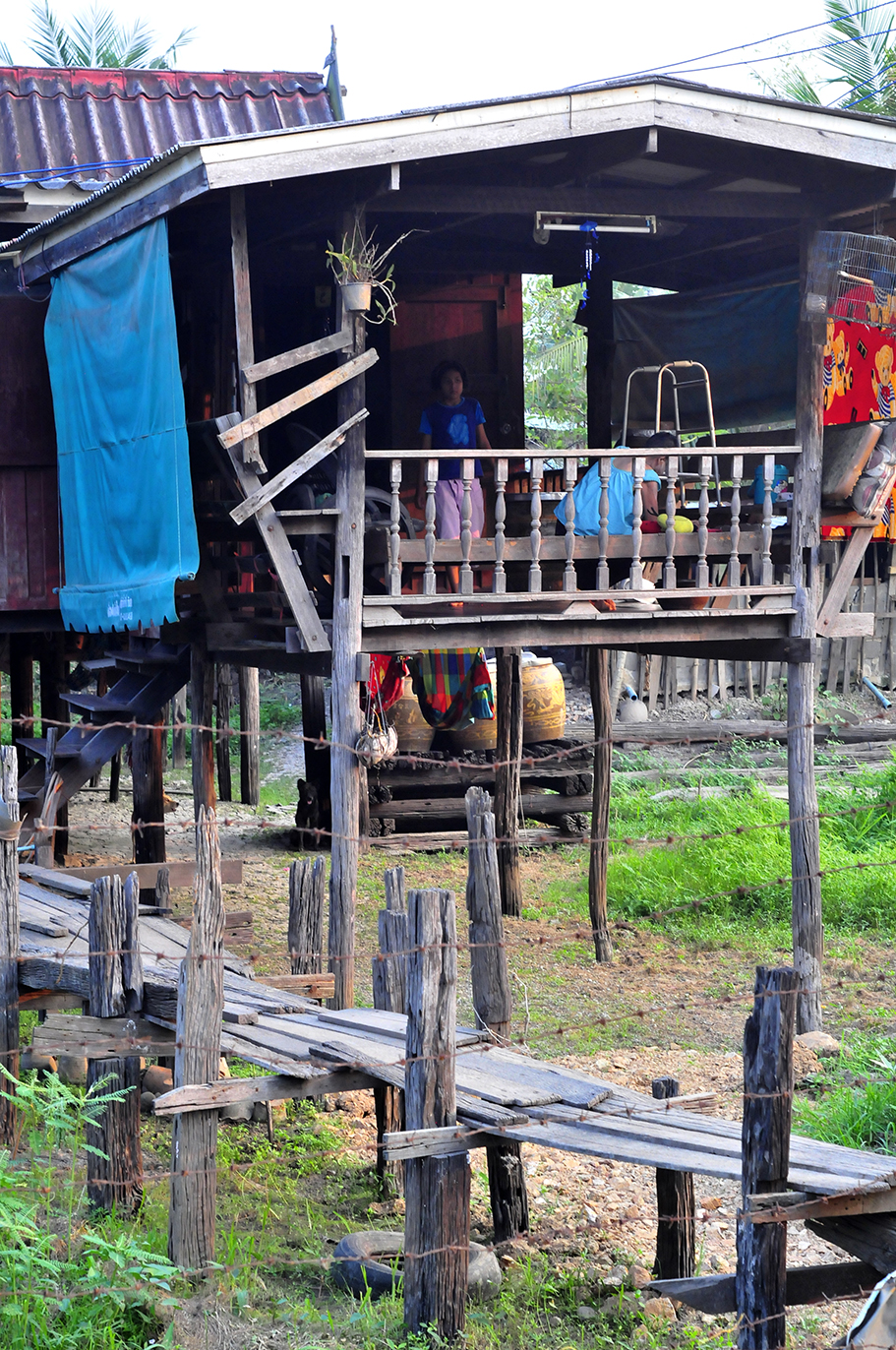 A photograph of a home built of wood lifted several feet off the ground on stilts.