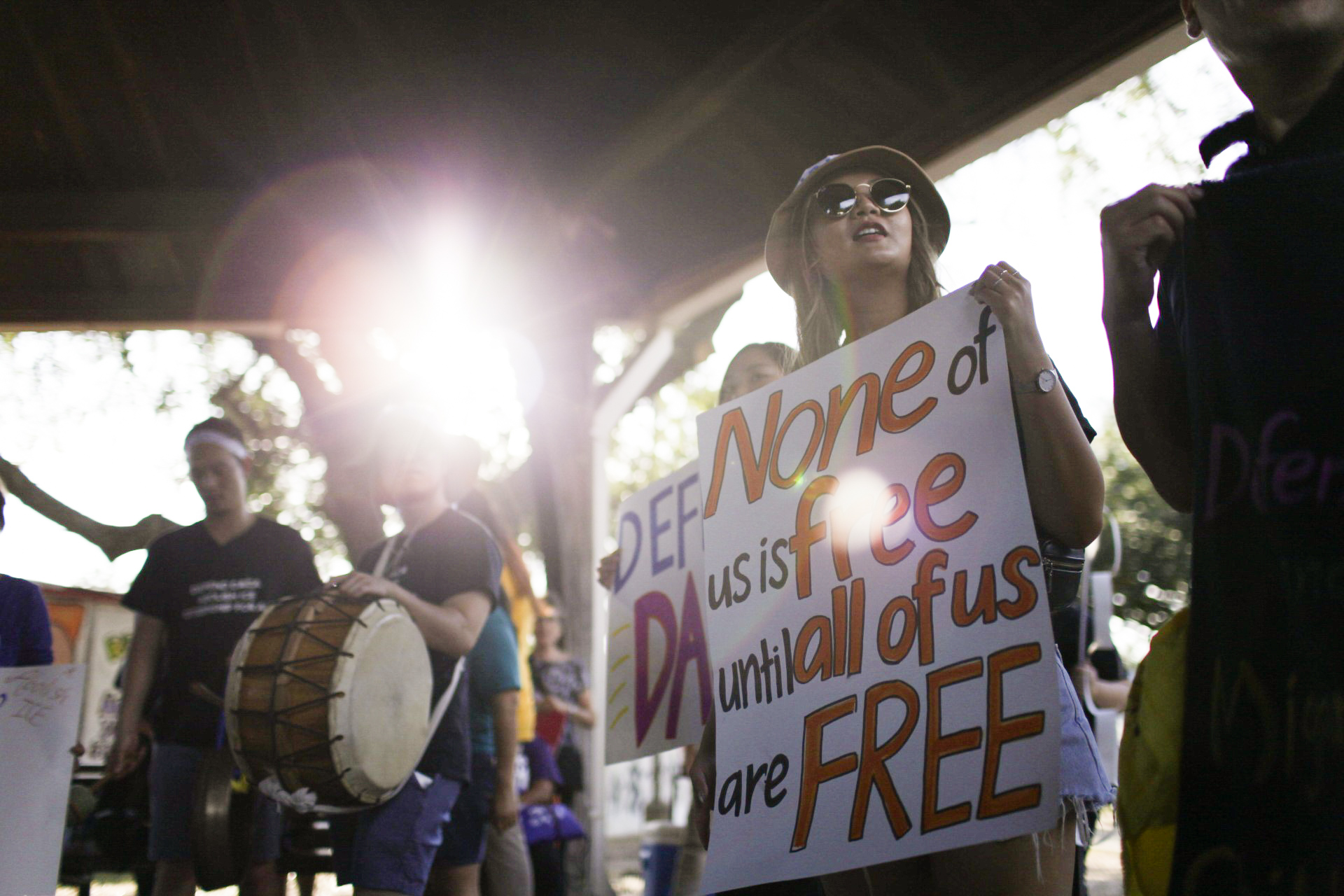 """Protesters holding drums and signs, one sign reading """"None of us is free until all of us are free."""""""