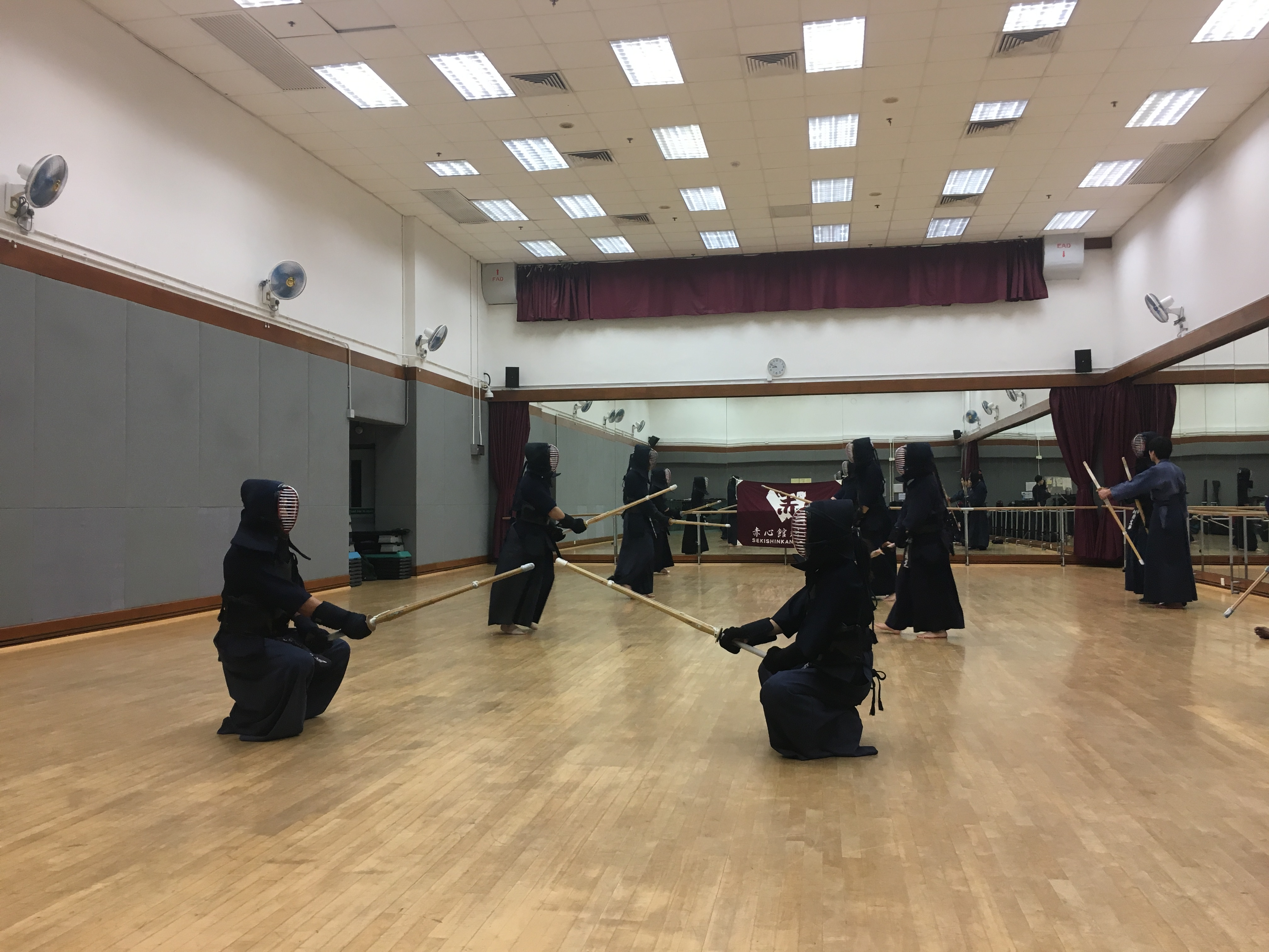 Photo of a practice room with numerous people in kendo gear.
