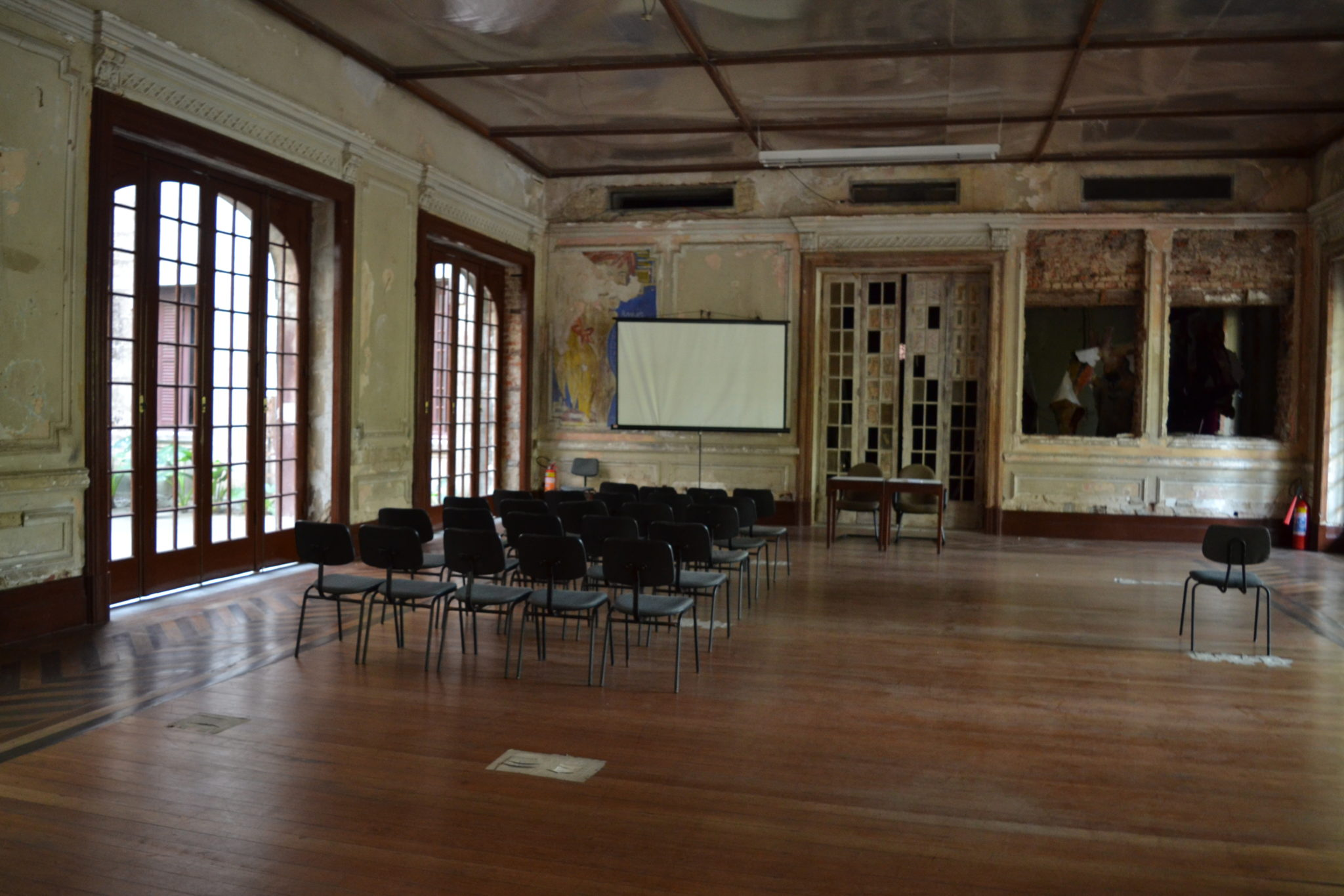 An old, empty meeting room with black chairs and a projector screen.