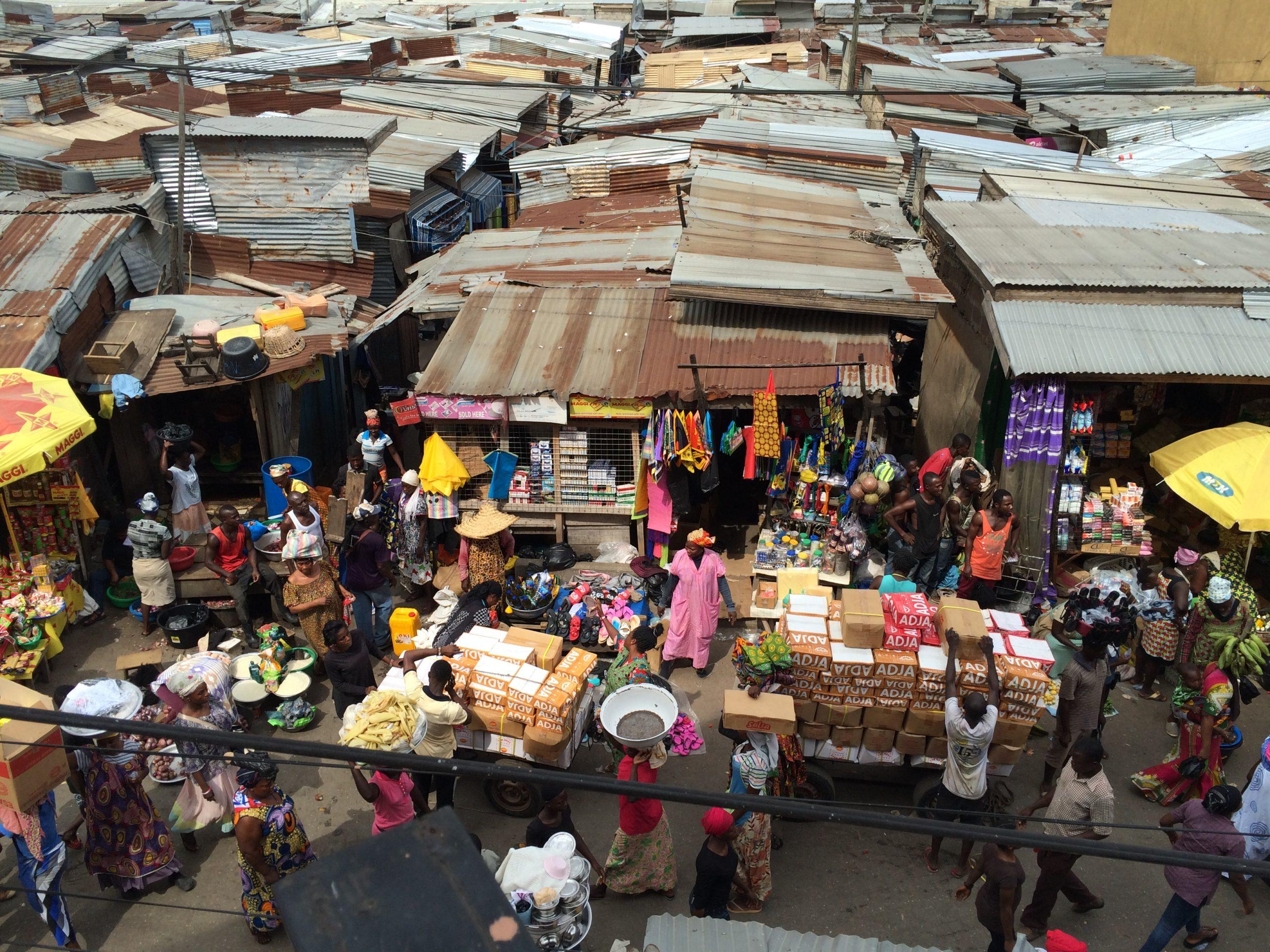 Goods, market traders, and corrugated iron stalls at Kumasi Central Market.