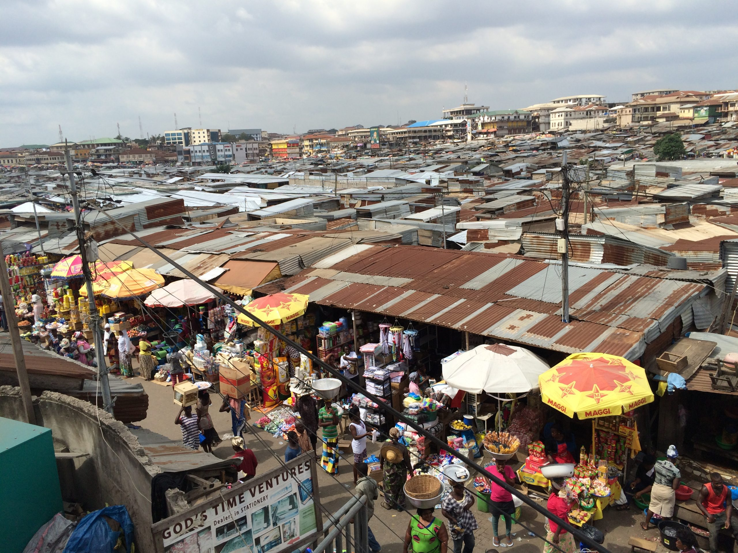 Men and women carry baskets and boxes of goods on their heads on a busy street in Kumasi Central Market.