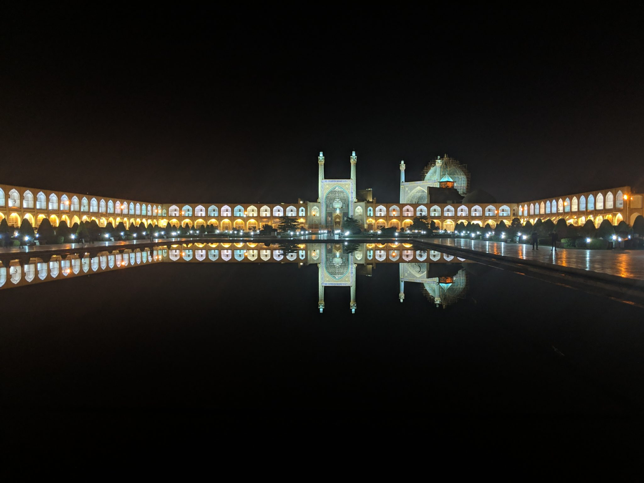 A large public square and mosque lit at night with pink, golden, and turquoise lights.