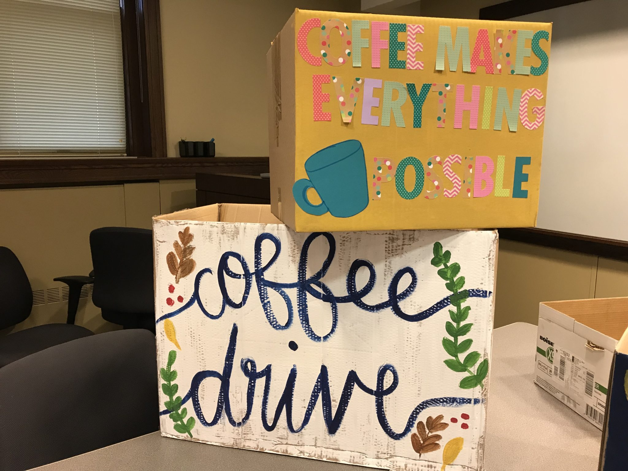 Two decorated cardboard boxes for the collection of donated coffee are stacked on a table