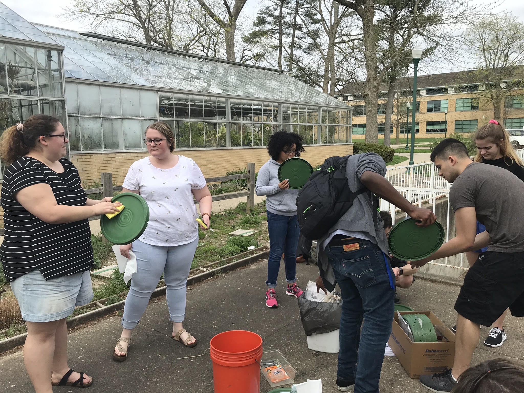 Six students stand outside and clean compost bucket lids