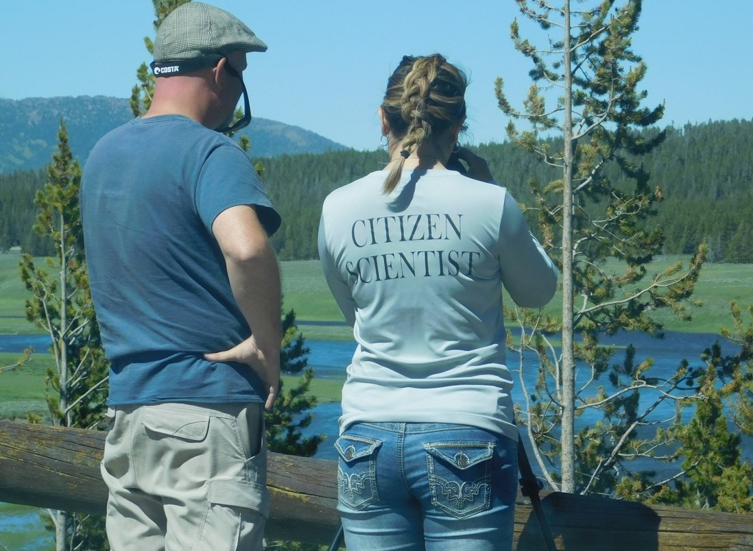 Photograph of two people standing at one of the Hayden Valley Overlooks in Yellowstone National Park.