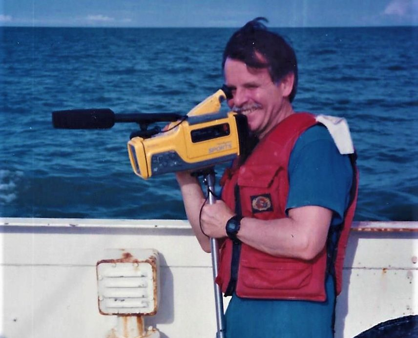 Photograph of a person on a boat holding a video camera.