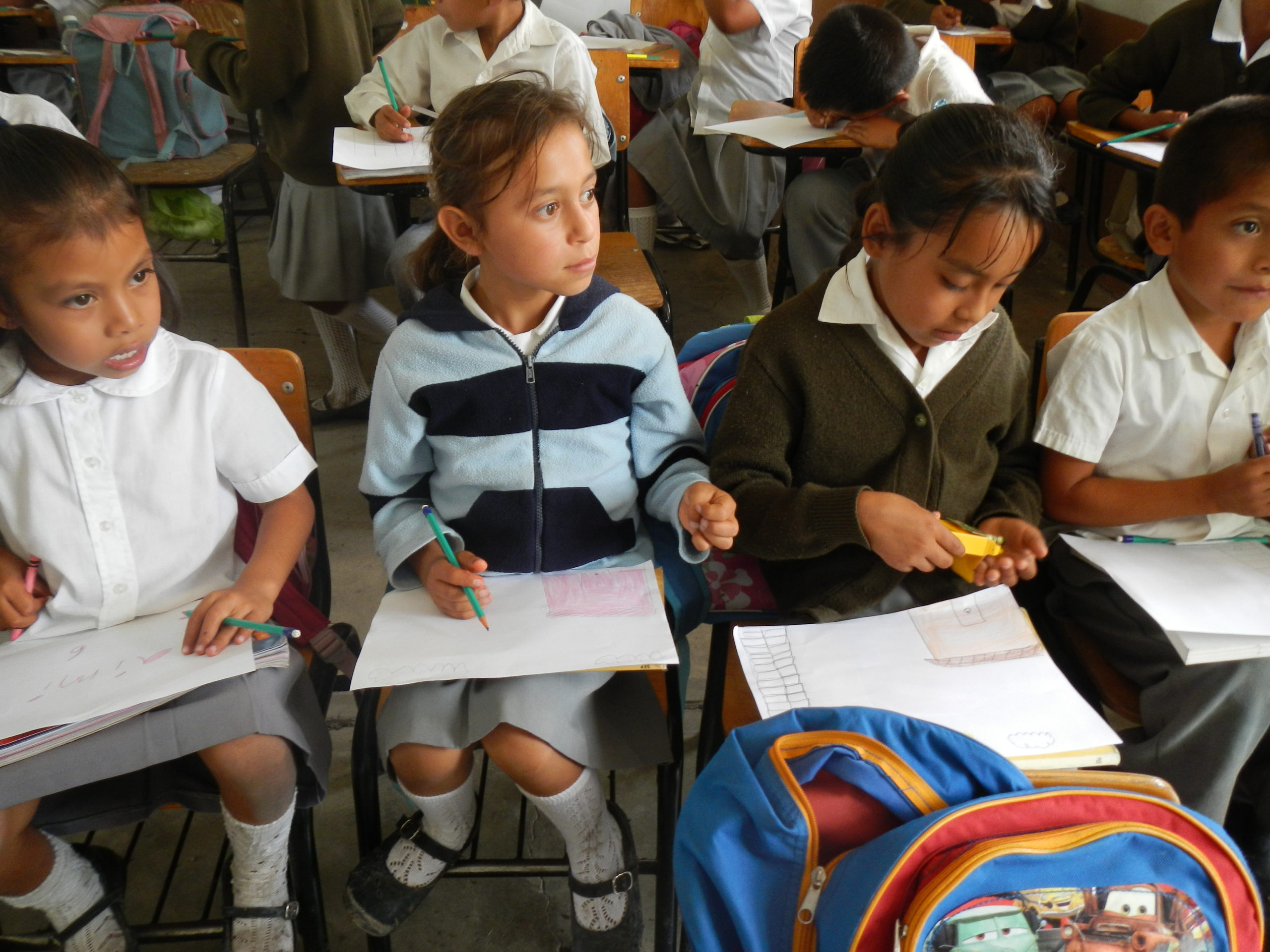 A color photograph of elementary-aged students in a classroom in Puebla, Mexico.