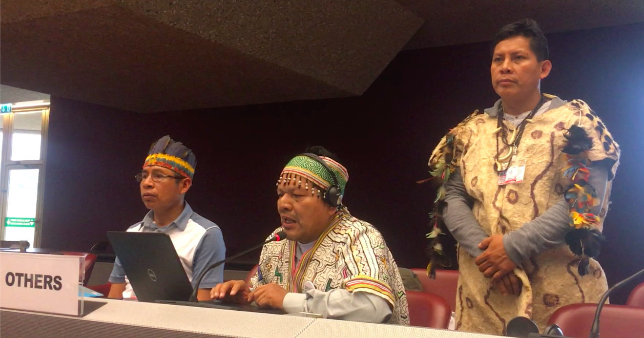"""Three indigenous men sitting at a table, called """"Others."""""""