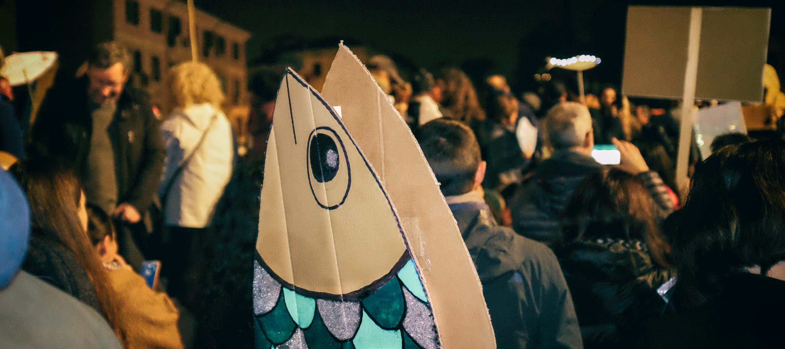 Photograph of protestors holding up sardine-shaped signs at a flash mob in Verona, Italy.