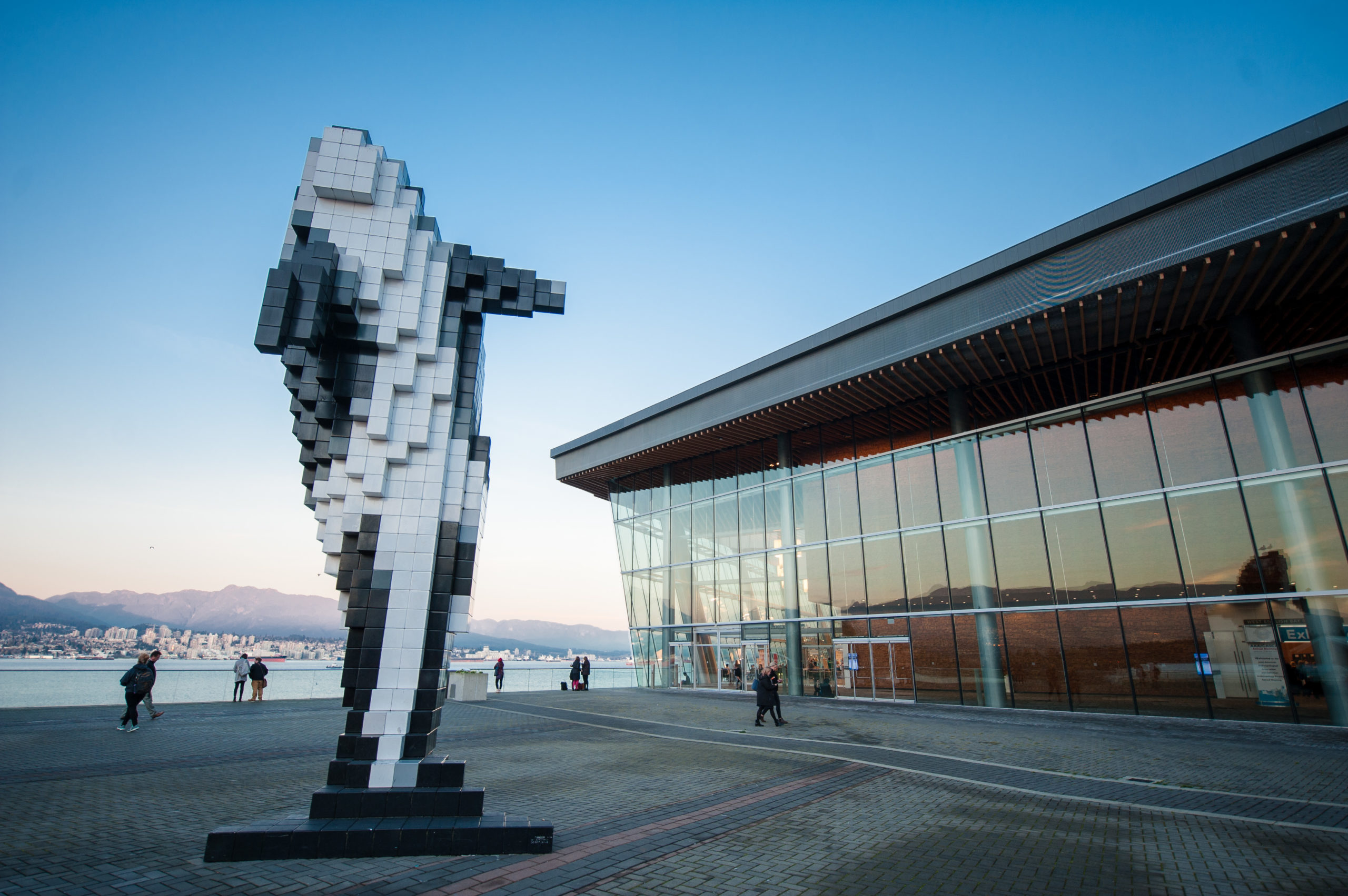 Photo of a courtyard and whale statue outside of the Vancouver Convention Center.
