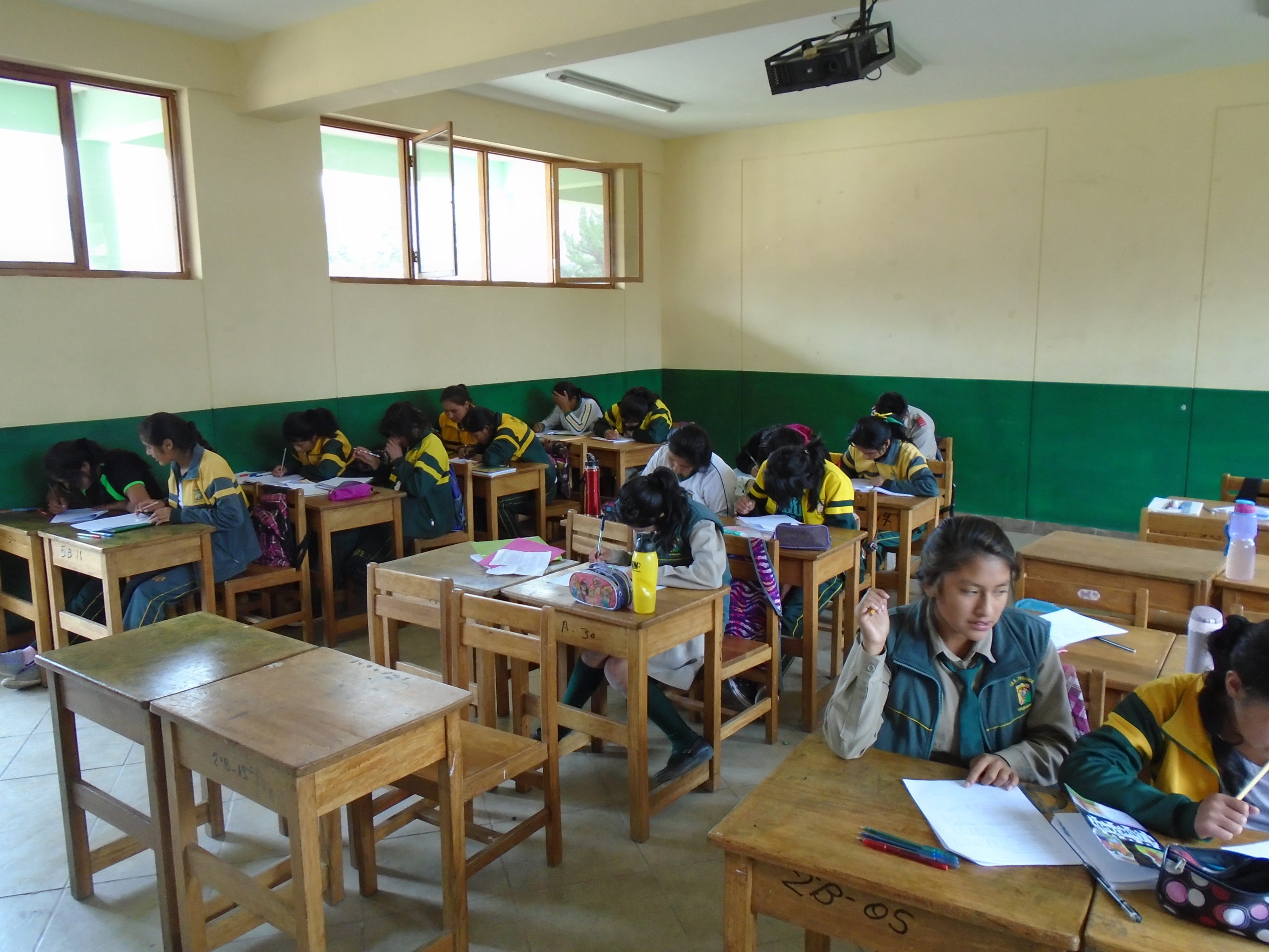 Picture of Peruvian students in a classroom with bare walls and wood desks.