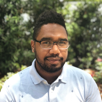 A photograph of David Caicedo, an Afro-Colombian man with a beard, glasses and wearing a collared shirt. Behind him are trees.