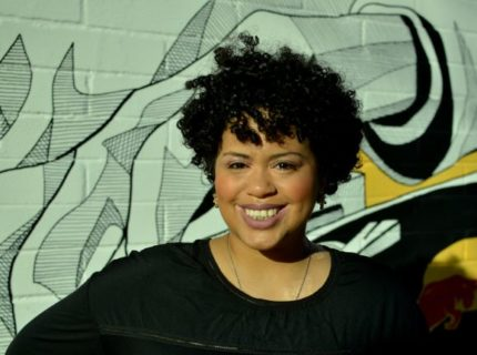A photograph of Denise Diaz, a Black Latina woman, smiling, wearing a black shirt, and standing in front of a mural