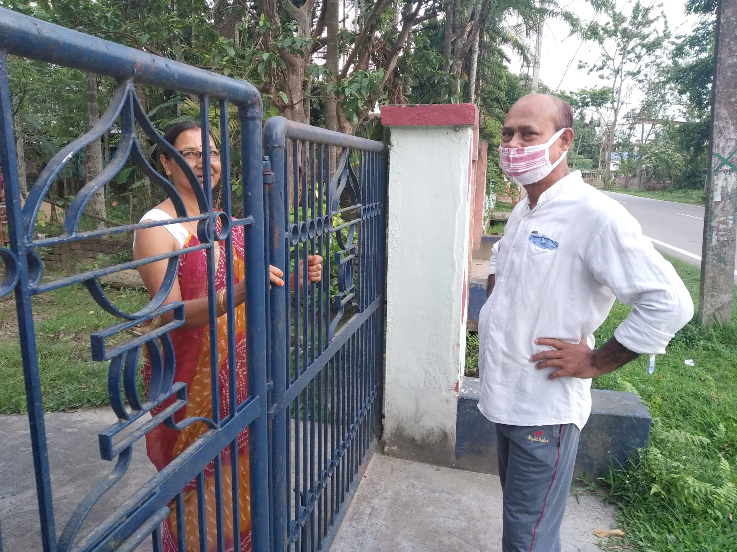 A photograph of two people interacting across a blue gate.