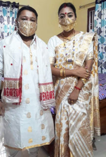 Photograph of a masked bridal couple.
