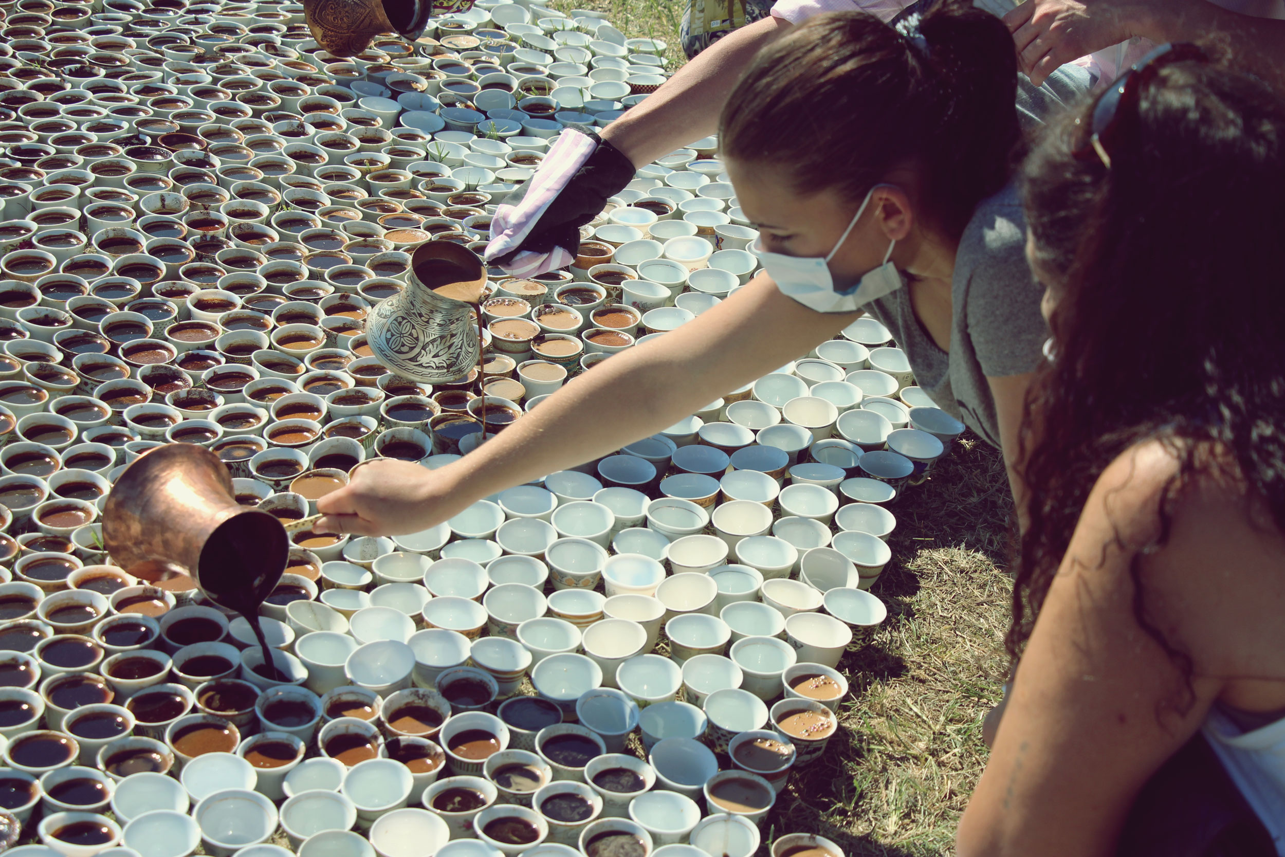 A photograph of people pouring liquid into cups.