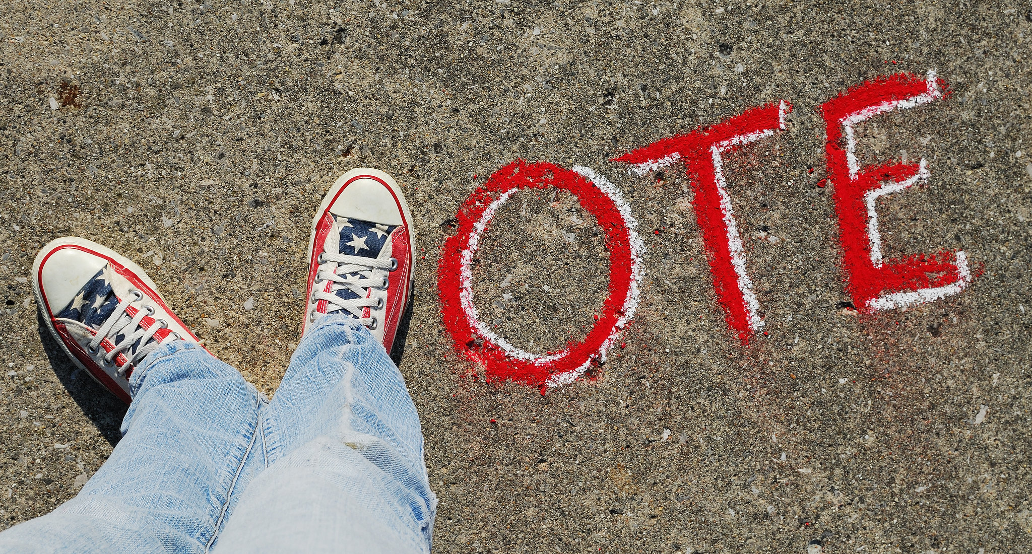 """Photograph of two feet in red, white, and blue sneakers compose the letter """"V,"""" followed by """"ote"""" in sidewalk chalk."""