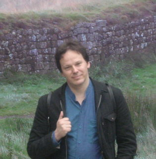 Photograph of a man standing in front of a wall