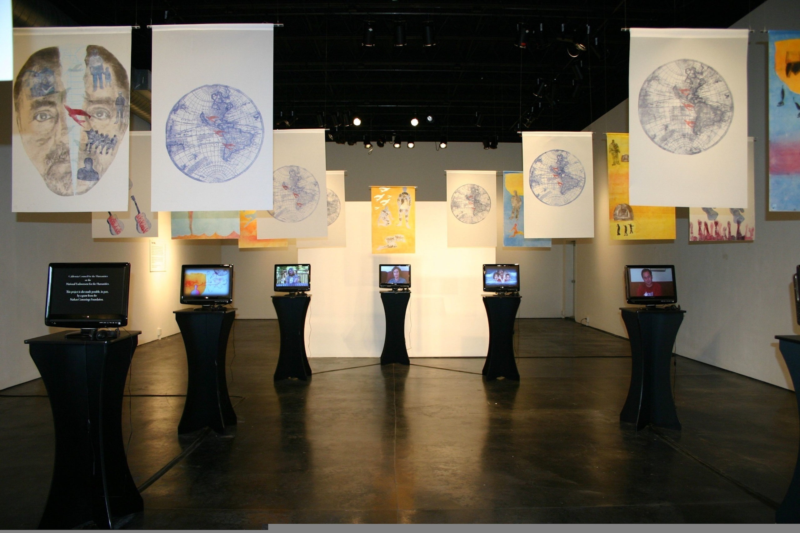 Photograph of a room with monitors and banners hanging from the ceiling.
