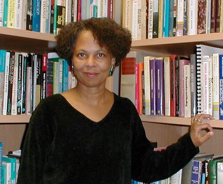 Picture of a Black woman in front of a bookcase