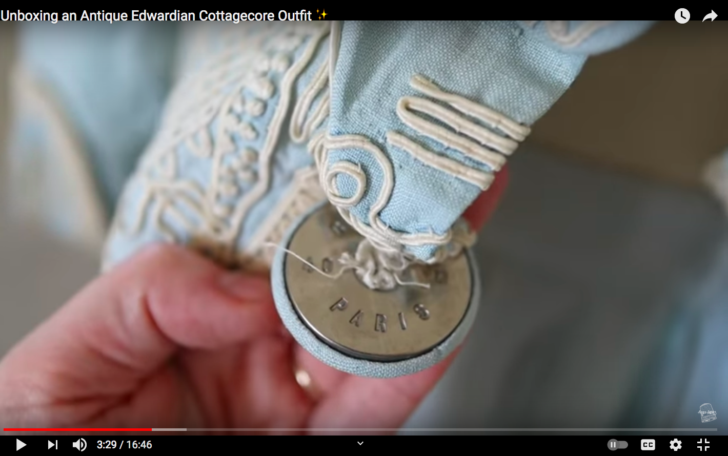 YouTube still of a metal button inscribed with the term 'Paris' on an Edwardian outfit