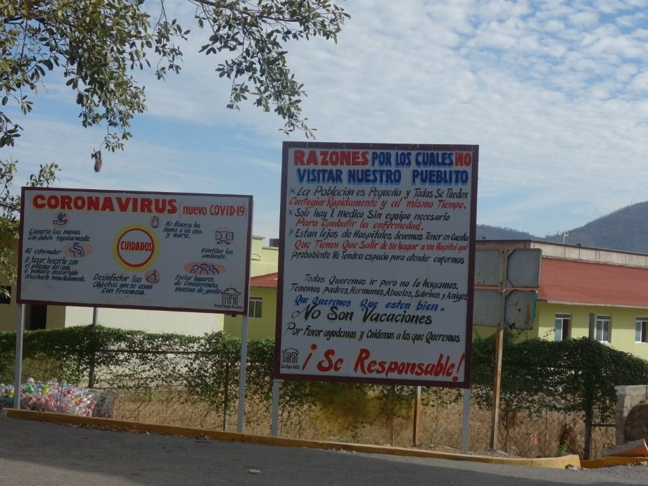 A picture of two signs that provide information about COVID-19 in a community.