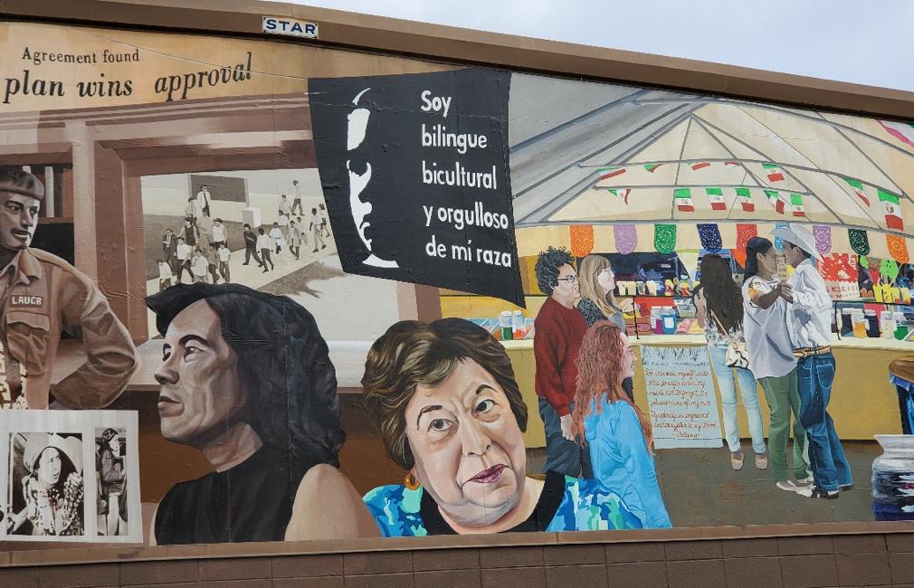 Photograph of a mural with image of Graciela de La Cruz underneath a sign of Latinx pride.
