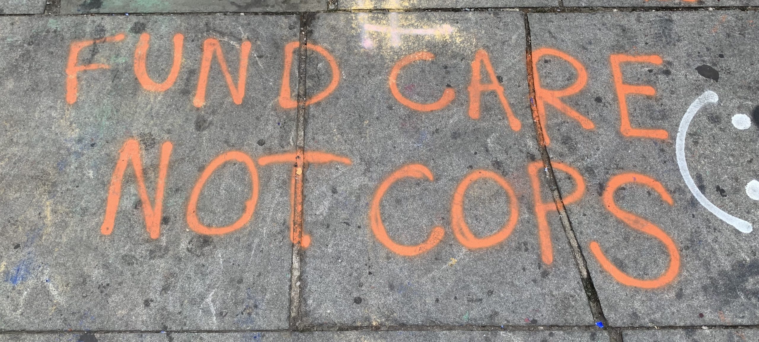 """A picture of a message spray-painted onto a concrete sidewalk. The message says, """"fund care not cops."""""""