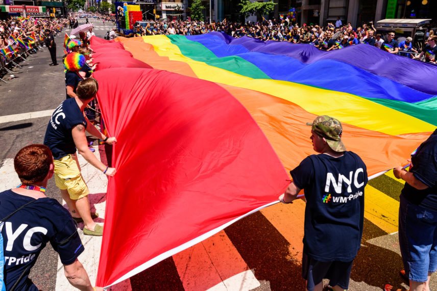 Photograph of multiple people holding an oversized rainbow flag