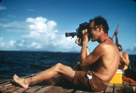 Photograph of of a person sitting with a video camera