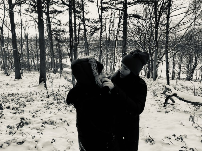 Black and white photograph of two people outdoors during winter