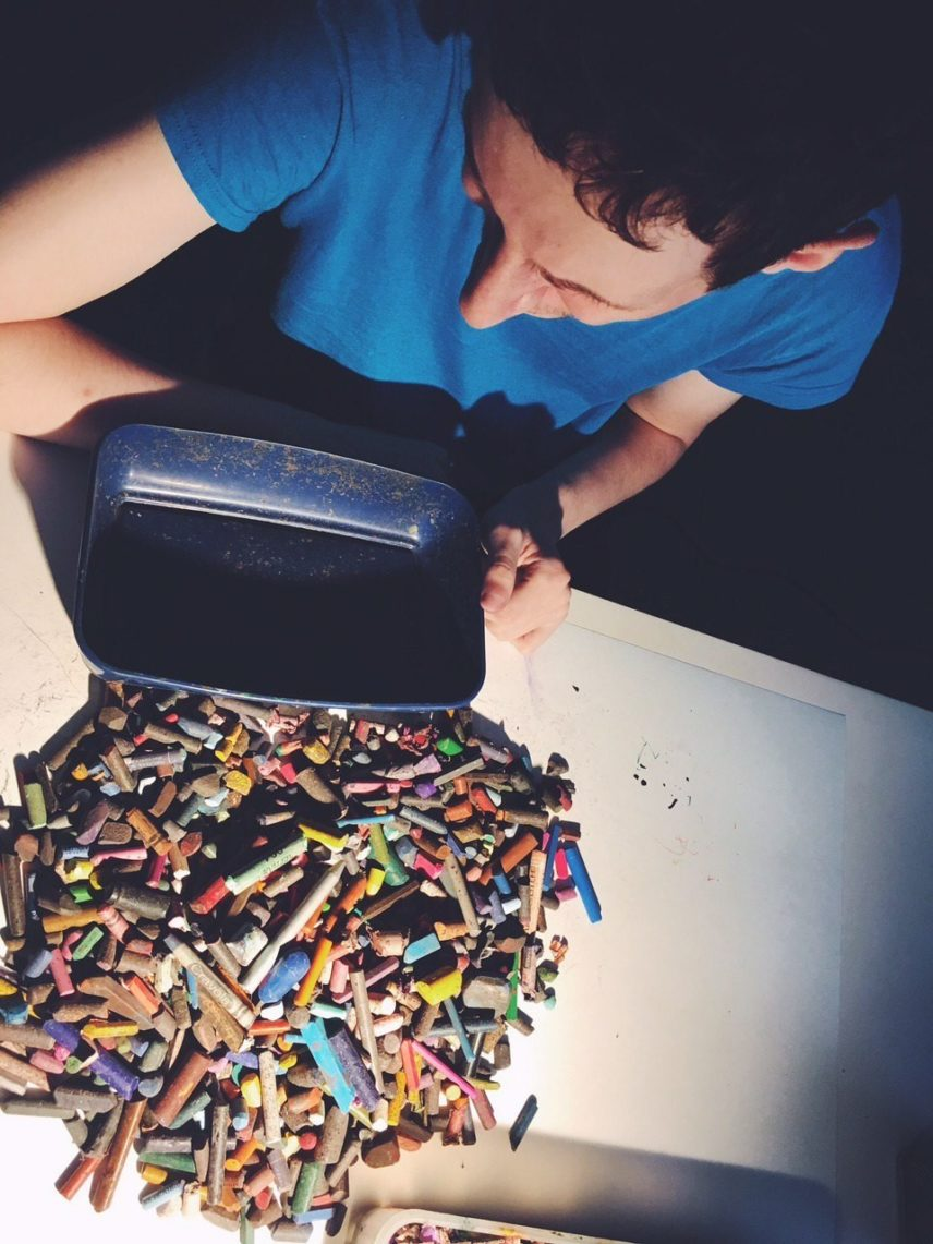 Photograph from above of a person with a pile of crayons and pastels