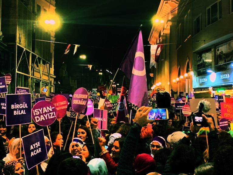 Women holding purple signs.
