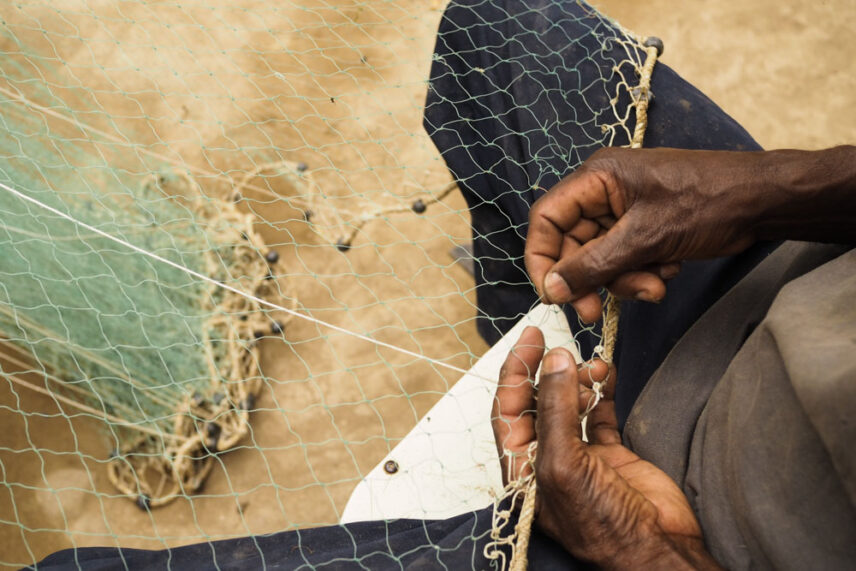 A picture of a man repairing his cast net