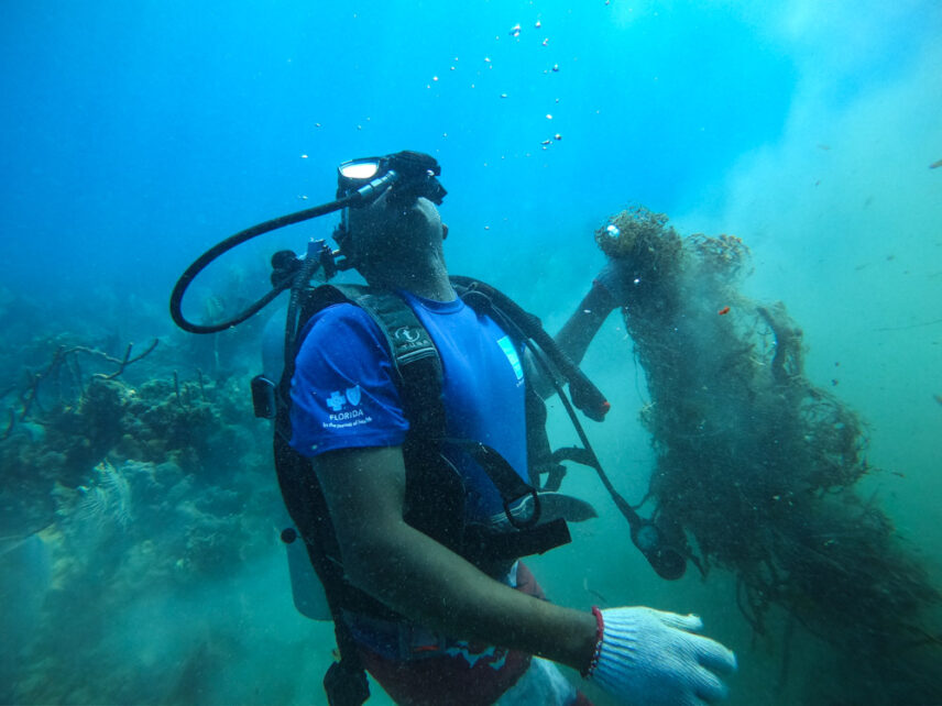 Photograph of a diver pulling up a ghost net from the seafloor